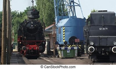 Loading steam locomotive with coal at railway station, platform