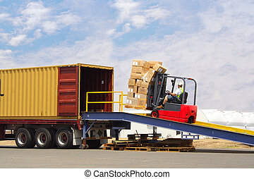 Loading Truck - forklift driver loading truck on a loading...