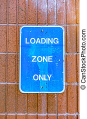 Loading zone only blue sign against brick