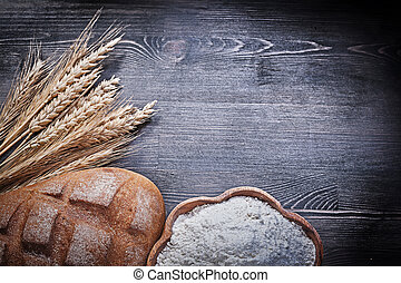 Loaf of bread golden wheat rye ears wooden bowl with flour on wo