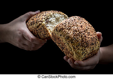 Loaf of bread in the woman hands on black background