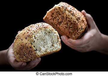 Loaf of bread in woman's hands on black background