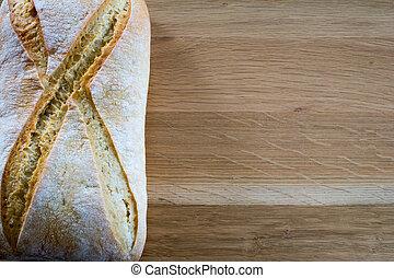 Loaf of bread on wooden oak table top.