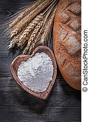 Loaf of bread wheat rye ears wooden bowl with flour on wood boar