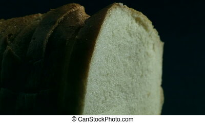 Loaf of fresh white bread cut in slices on wooden background