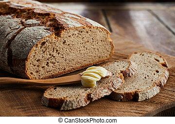 Loaf of sliced rye bread with butter spreader