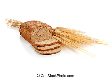 Loaf of wheat bread and shocks of wheat