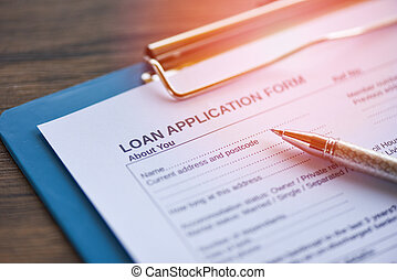 Loan application form with pen on paper / financial loan negotiation for lender and borrower