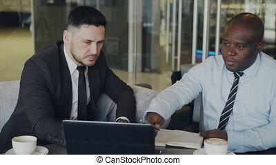 lobby., sien, vitreux, business, pointage, africaine, ordinateur portable, moderne, démarrage, cahier, écriture, projet, entrepreneur, américain, informatique, hommes affaires, ambitieux, complet, associé, discuter, caucasien