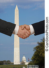 Handshake in Washington DC with the Washington Monument and Capitol Hill in the background