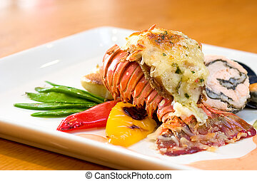 Delicious meal of lobster and stuffed chicken served with sweet peas, potatoes, peppers and oysters.
