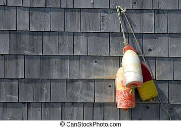 Old Fishing Buoy's Nailed To Shingled Wall