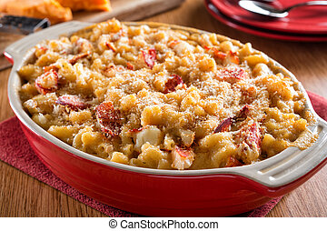 A delicious homemade lobster mac and cheese casserole on a wood table top.