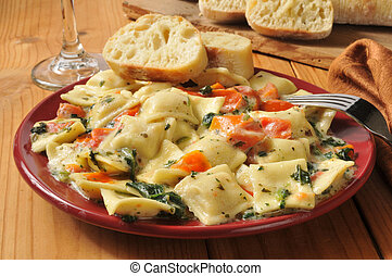 Lobster and ricotta ravioli with spinach and tomato in a buttery cream sauce