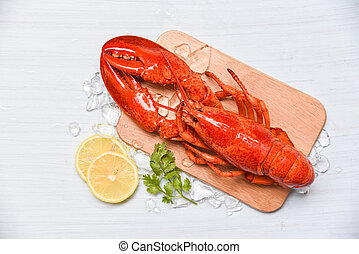 Lobster seafood with ice on wooden cutting board and lemon coriander - Close up of steamed lobster food