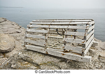 Lobster trap on the rocks with a fishing boat in the ...