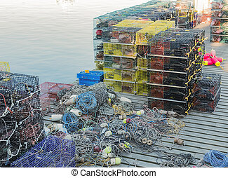 Lobster traps with rope and buoys stacked on a pier - Many ...