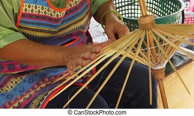Local woman assembles the handmade wooden frames of traditional, Thai, paper umbrellas using string, in a Chiang Mai artisans workshop. Video UltraHD 4k