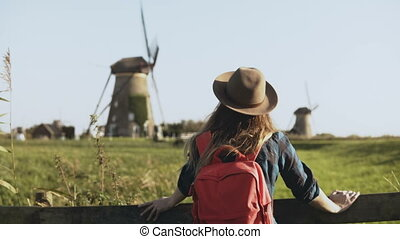 Local Caucasian girl stands near windmill farm. Village woman in hat with long hair and red backpack looks around. 4K