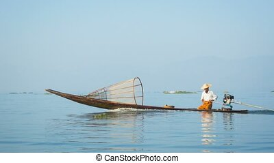 Local fisherman floats on fishing boat with a motor. Inle lake, Burma (Myanmar)