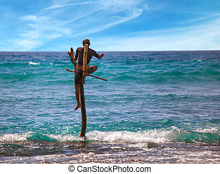 Local fisherman is fishing in unique style stilt fishermen