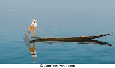 Local fisherman on the boat with fish trap. Inle Lake, Myanmar