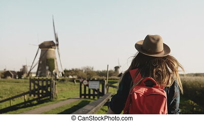 Local girl slowly walks up to a windmill farm. Woman in hat...