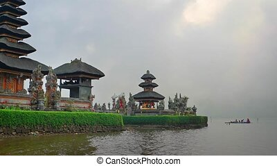 Group of local worshipers approaching Pura Ulun danu Bratan, a lakeside Hindu temple with tiered pagodas, by boat.