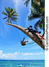 Local kids swinging on a rope swing in Lavena village, Taveuni Island, Fiji