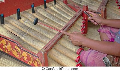 Local musicians in old fashioned costume strike traditional, bamboo percussion pipes with rubber mallets in Bali, Indonesia.