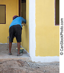 Local painter is painting the house wall.