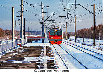 Local passenger train approaches to the station at winter morning time.