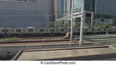 Urban trains track in Tokyo local train running on a parallel track, motion view from another train
