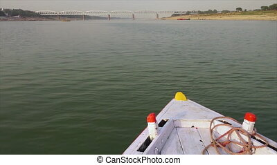 Local wooden boat sailing on Ganga River, India - Wide...