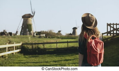 Local young girl walks around old windmill farm. Cowgirl in hat with long hair and red backpack wanders thoughtfully. 4K