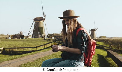 Local young woman sits near old rustic mill. Cowgirl in hat with long hair and red backpack makes a flower bouquet. 4K