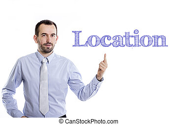 Location - Young businessman with small beard pointing up in blue shirt