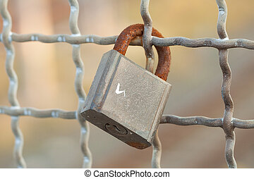 Lock - A rusty iron closed lock to an iron mesh
