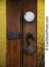 Lock with open padlock of an old wooden door