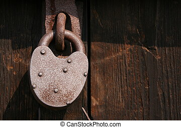 Locked door - Old rusty pad lock on wooden door.