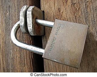 Locked - Padlock closing a wooden door