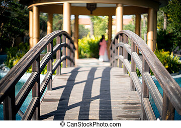 locked shot of arched wooden bridge with swimming pool on both sides with blue water and out of focus people in the distance moving and enjoying the vacation in this resort
