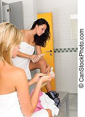 Locker room two sportive women applying lotion wrapped in...