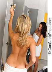 Locker room two sportive women going shower wrapped in ...