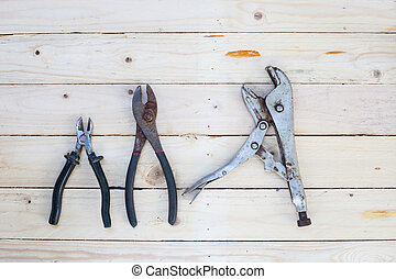 Locking pliers on white wooden floor