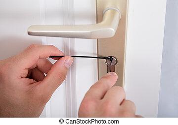 Lockpicker Hand Fixing Door Handle At Home - Close-up Of...