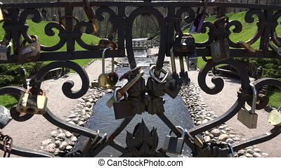 Locks of newlywed married hanging on retro bridge railing and beautiful river brook flowing on sunny day. Ancient tradition. Symbol of never ending love. Static shot. 4K UHD video clip.