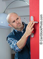 locksmith man fix the door with a screwdriver