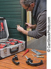 Locksmith repair the lock of a door of the house with a...