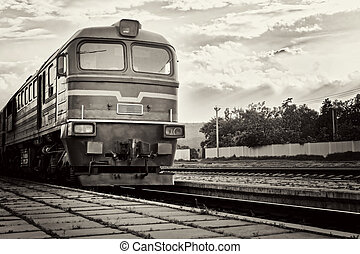 locomotive arrives at the station on the background of a stormy sky, black and white